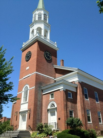 A brick church with a tall white steeple.
